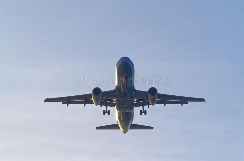 Looking up on the commercial passenger airplane. Landing gear extracted, short before landing, blue sky as background royalty free stock images