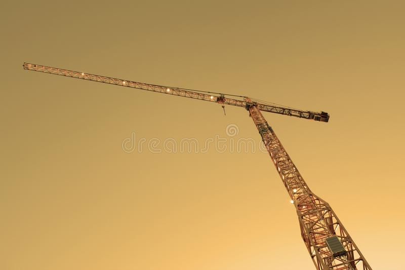Looking up at construction crane against golden sky. Looking up at a high yellow construction crane in a golden light against the sky stock photos
