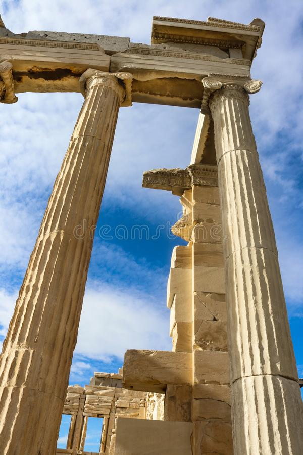 Looking up at a corner of the parthenon that has been repaired against an intensely blue sky with whispy clouds. Looking up at corner of the parthenon that has stock photo