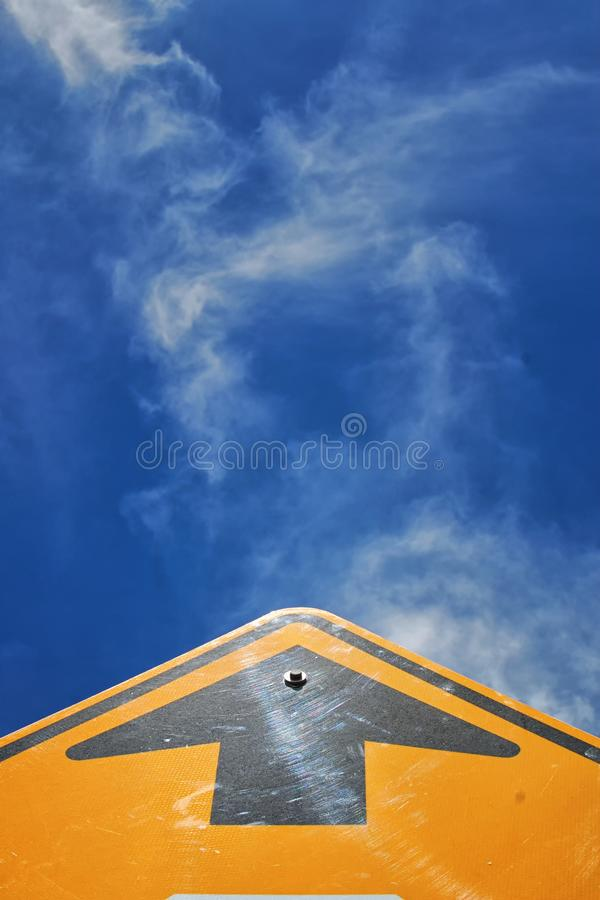 Looking up or go straight down the road. A yellow street sign with a black arrow on it indicates to go straight forward, but also says to go onward and upward stock photo