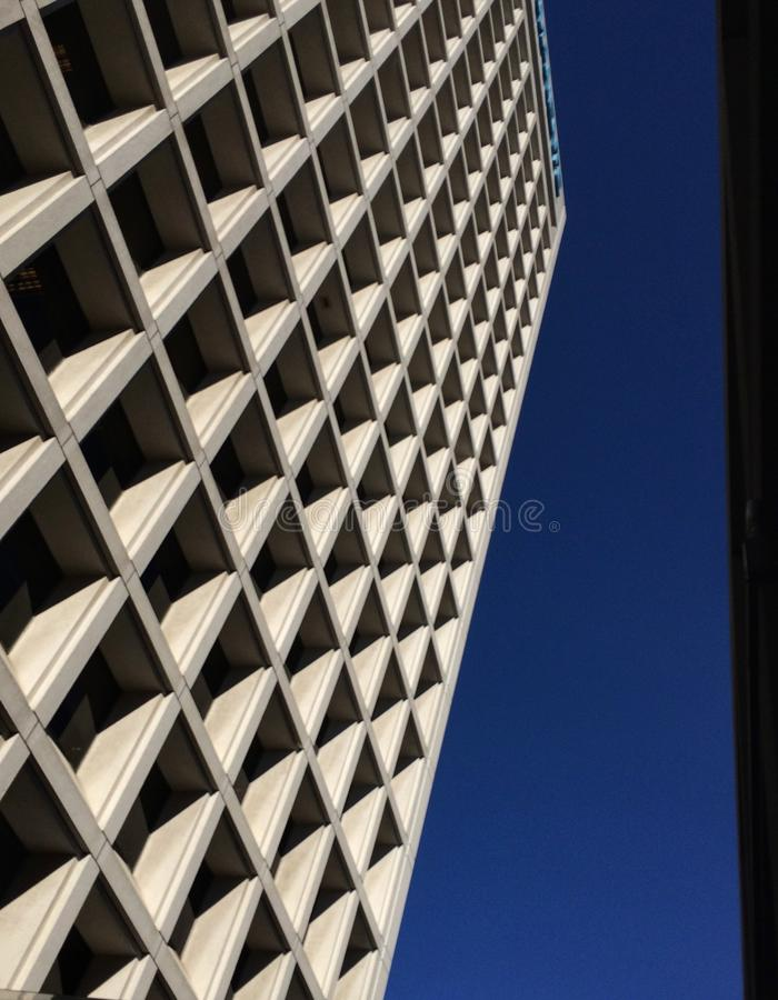 Looking up at high rise building. Looking up at a high rise building, blue sky, windows make abstract grid pattern stock photos