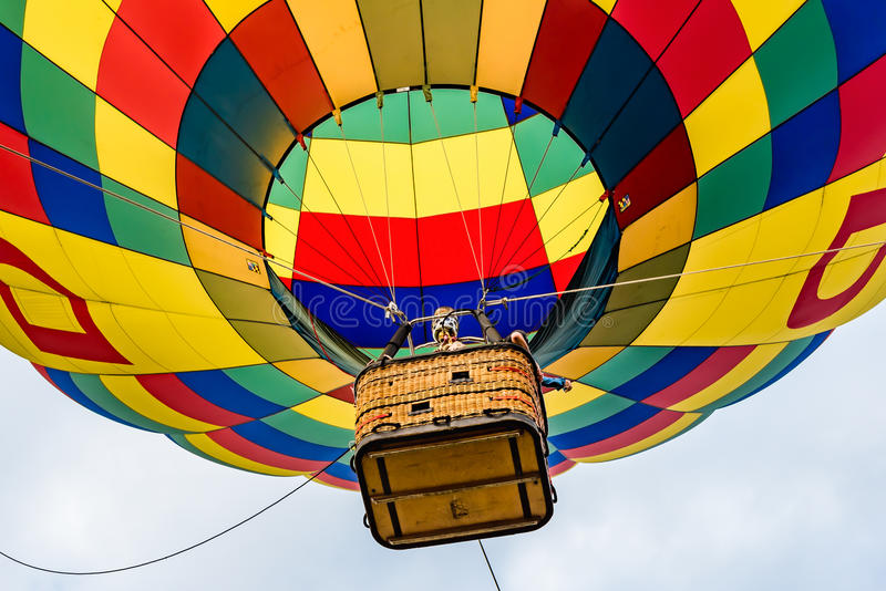 Looking Up at a Hot Air Balloon. View from the ground looking up at the basket of a hot air balloon stock image