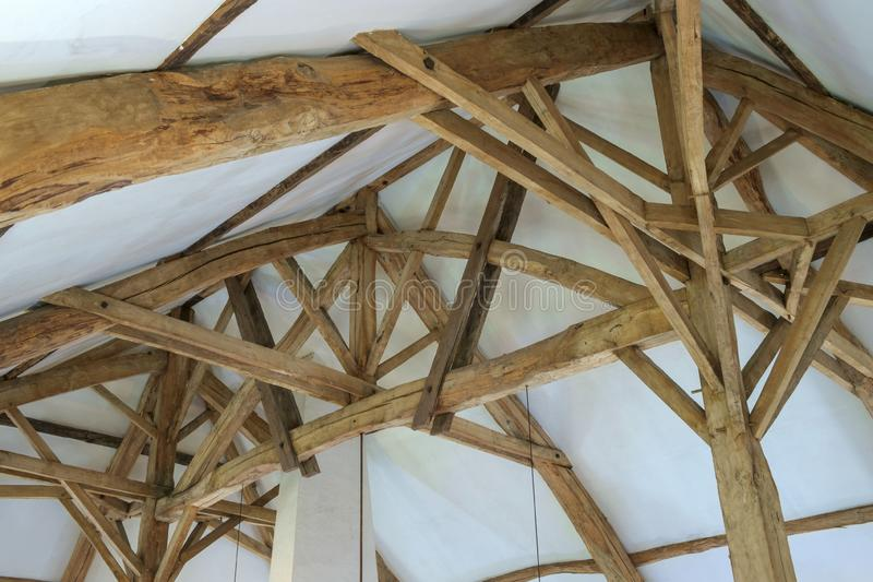 The the massive restored interior timber roof construction in a large  old French farmhouse royalty free stock photo
