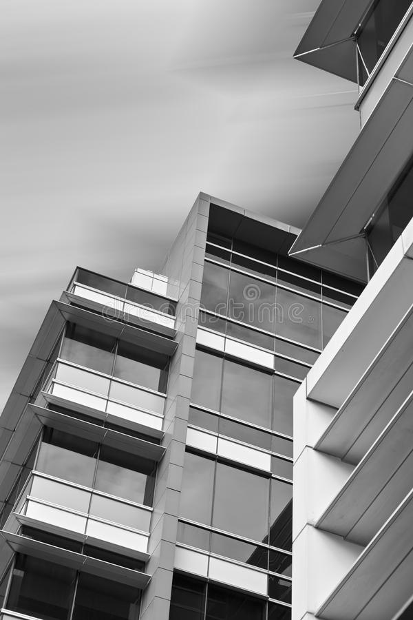 Looking up at modern office building against smooth cloudy sky royalty free stock photo