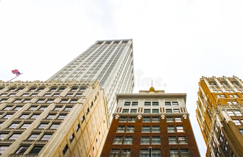 Looking up at ornate art deco buildings with an American flag flying on one stock images