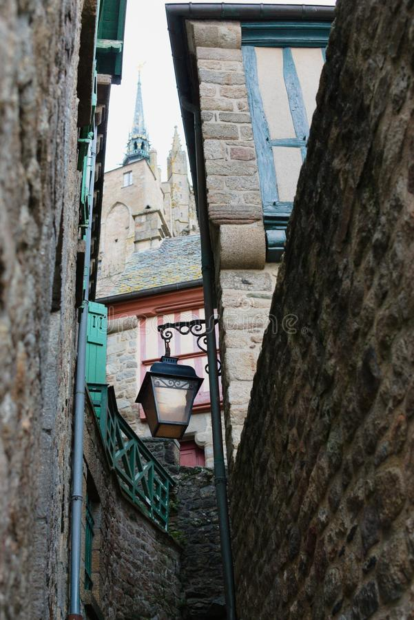 Looking up through dark alleyway onto Mont Saint-Michel abbey tower beautiful lantern old style vintage royalty free stock image