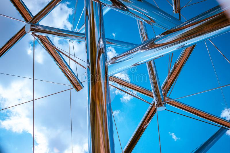 Looking up at the sky through a chrome statue royalty free stock photography