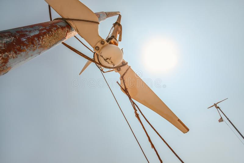 Looking up small broken wind turbine, strong midday sun shining in back.  stock photos
