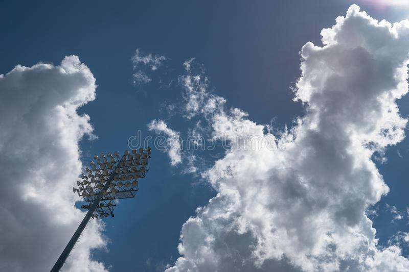 Sports stadium lights against a partially cloudy sky stock images