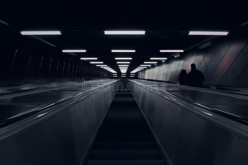 Looking up in subway escalator. In Stockholm. Lines of light and the dark silhouette of a couple stock photo