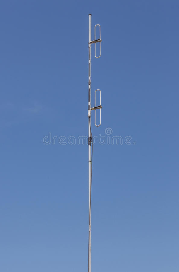 Looking up the telecommunication dipole antenna with blue sky ba. Ckground royalty free stock photography