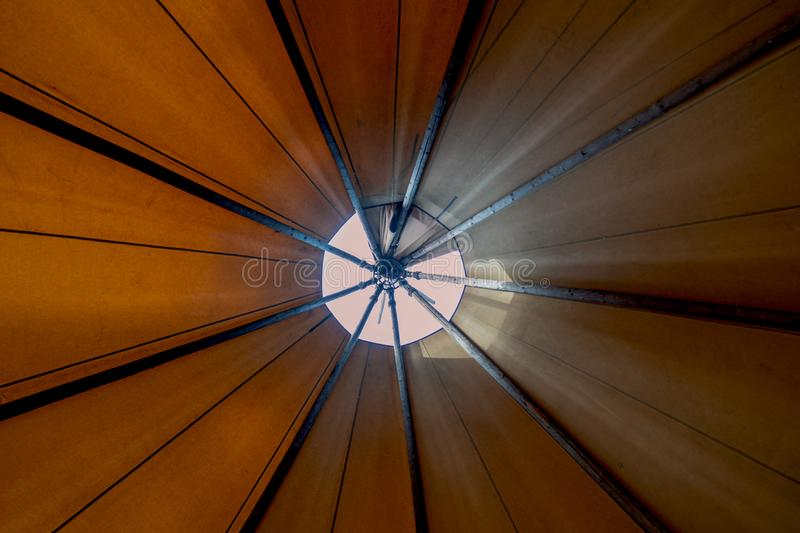 Looking up towards teepee-ceiling from inside the tent shows bright day light filtering in creating a cozy ambience. Looking up towards the smoke hole window royalty free stock image