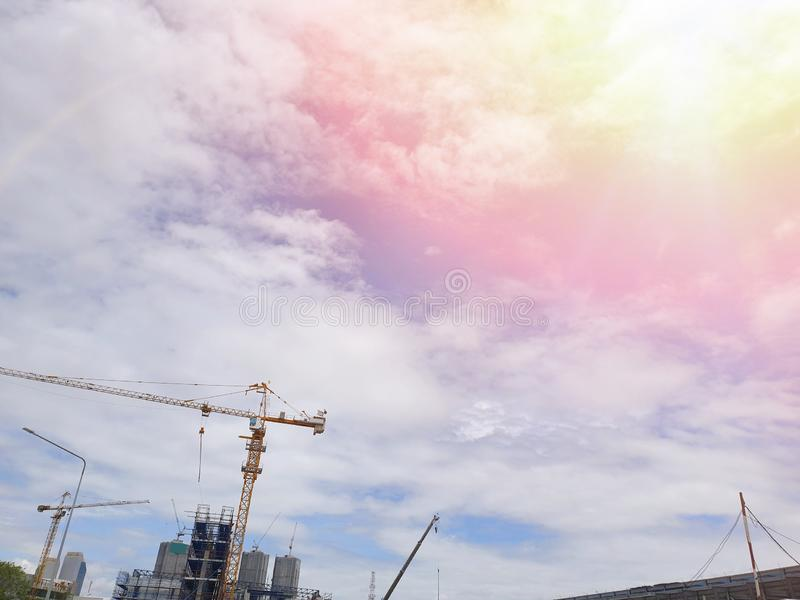 Looking up of tower crane on sky and cloud with sun shining as a background royalty free stock image