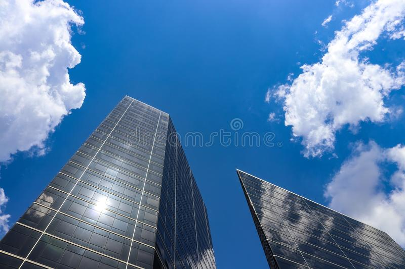 Looking up at modern buildings with reflections and a very blue sky with fluffy clouds. Looking up at two modern buildings with reflections and a very blue sky royalty free stock photos