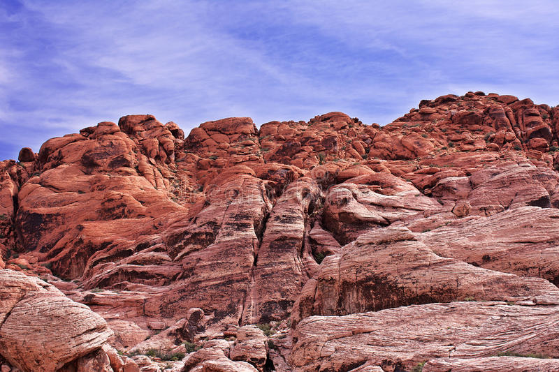 Looking upward at a cliff of jagged, craggy rocks with a blue, cloudy sky in the background. Red Rock, Nevada. Looking upward at a cliff of jagged, craggy, red royalty free stock image