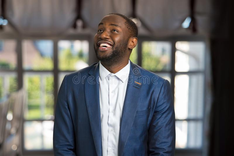 Looking upward and smiling businessman. Happy young afro american manager indoors. Natural smile and joy of handsome businessman royalty free stock image