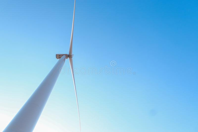 Looking upward to a big wind turbine and a blue sky. Alternative energy source, production and power generation. Ecology and freedom concept stock images