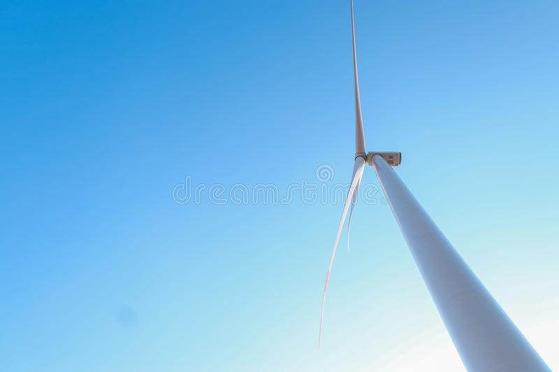 Looking upward to a big wind turbine and a blue sky. Alternative energy source, production and power generation. Ecology and freedom concept royalty free stock photography