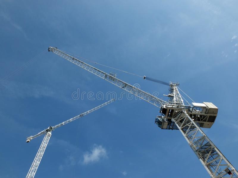 Looking upward view of two tall white construction cranes on a building site against a blue sky with clouds. A looking upward view of two tall white heavy stock photo