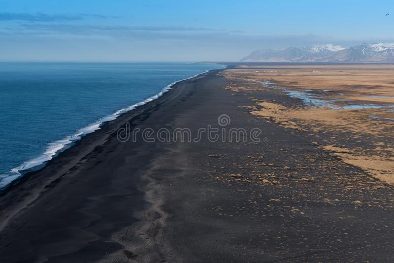 Looking west from Dyrholaey at the vast volcanic black sand beach. With mountains in the background stock images