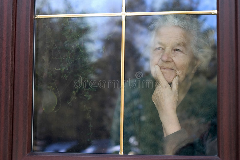Looking through the window. Elderly woman looking through the window