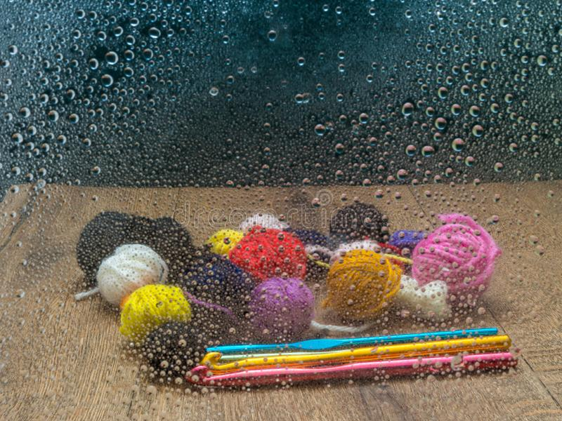 Leftover yarn on a wooden table with crochet hooks, seen through a window with rain drops. Looking in through the window. Small balls of left over wool on a stock image
