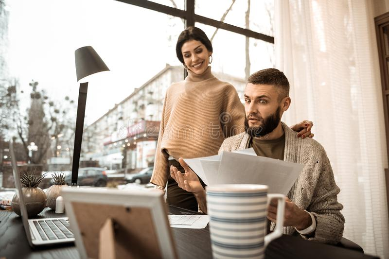 Shocked bearded guy carrying papers and showing them to his wife stock photo