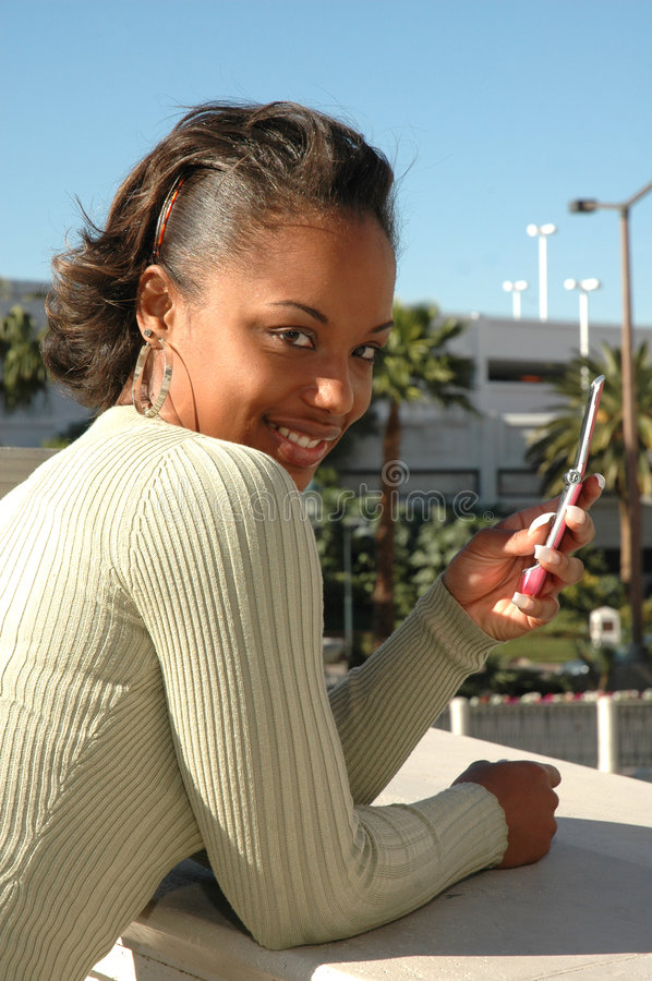 Looking at You. Beautiful Black woman standing outside in a city scene using her cell phone. Woman with expressions on her face as she uses her cell phone. Woman royalty free stock images