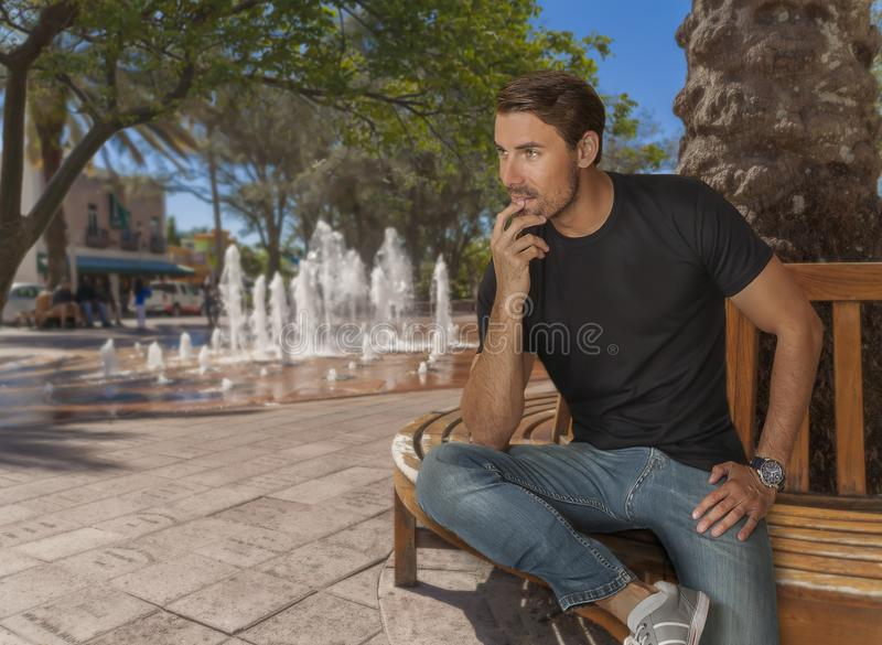 A handsome fit man sits on a bench at the city park by the water fountain. He looks away focused at someone in the distance. The in-ground water fountain is royalty free stock photography
