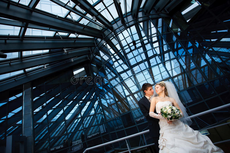 Looks of bride and groom. Bride and groom under the glass ceiling royalty free stock photo