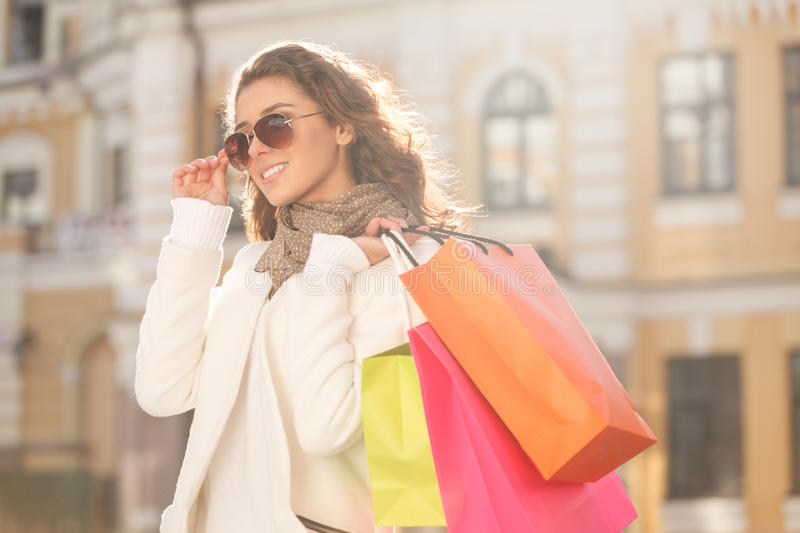 Looks great with her new sunglasses. Beautiful young women in sunglasses holding the shopping bags and looking away royalty free stock photos