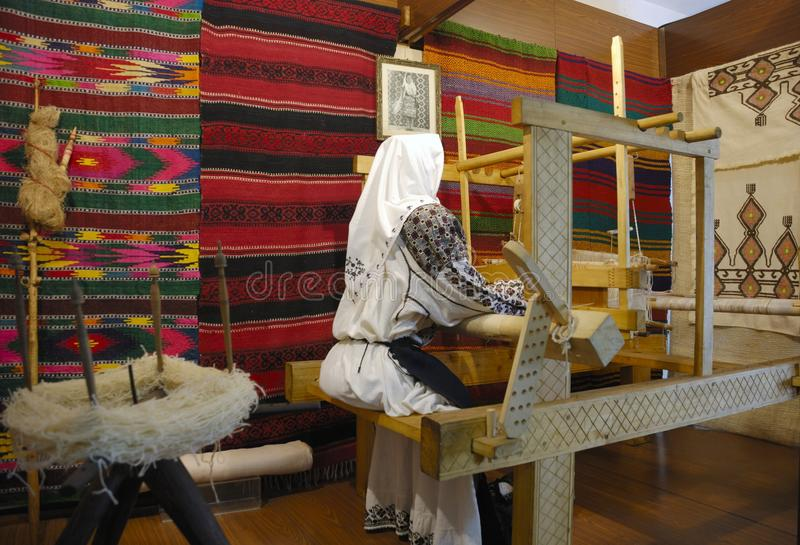 Loom. Woman weave at an old traditional romanian loom stock photography