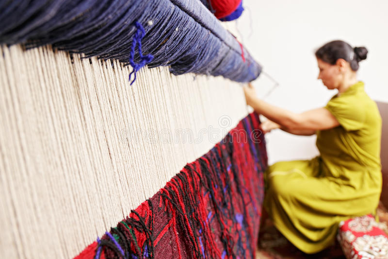 Loom. For hand weaving carpet with woman working at backstage stock photo