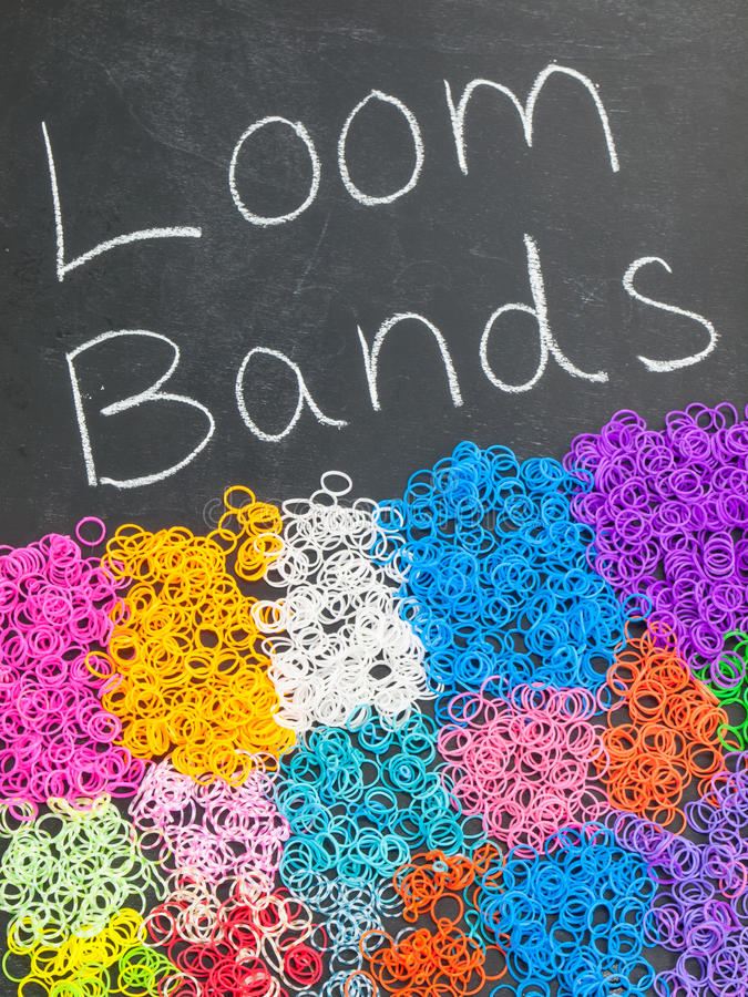 Loom bands on a blackboard. Multicolored loom bands on a blackboard with the text loom bands royalty free stock photography