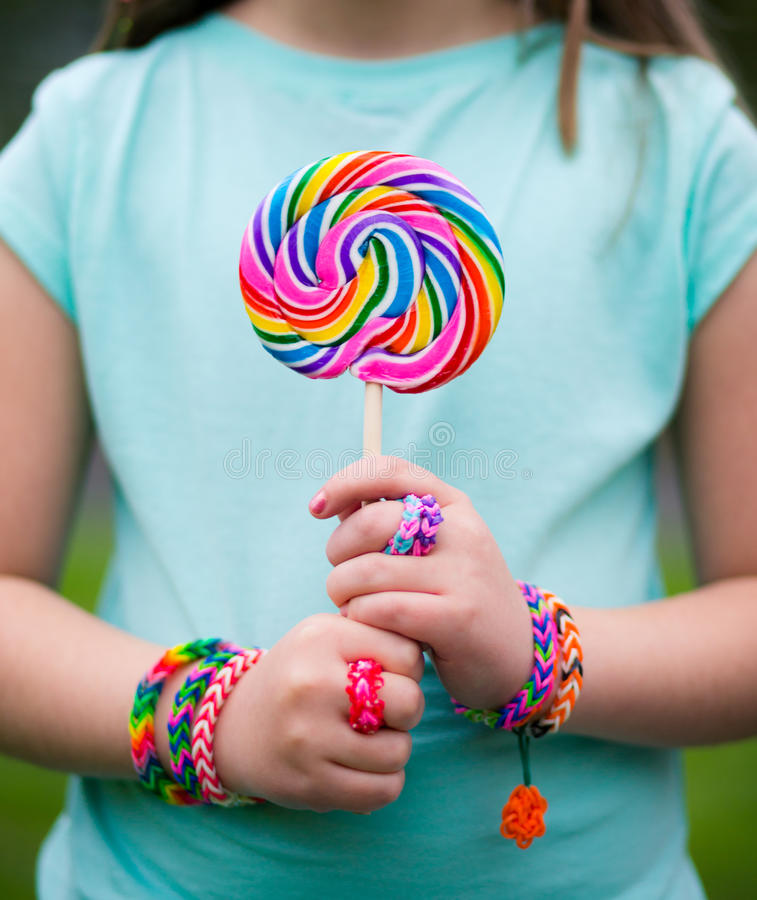 Loom bracelets. Young girl making wearing loom bracelets and rings holding a lollipop. Natural light. Young fashion concept stock image