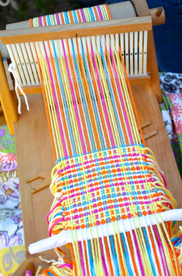 Loom. A weaving project in progress on a small hand loom royalty free stock photo