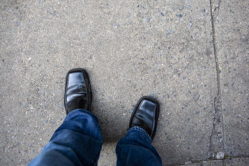 Loooking down at mans legs with blue jeans and black shoes on an urban city sidewalk walkway stock photo