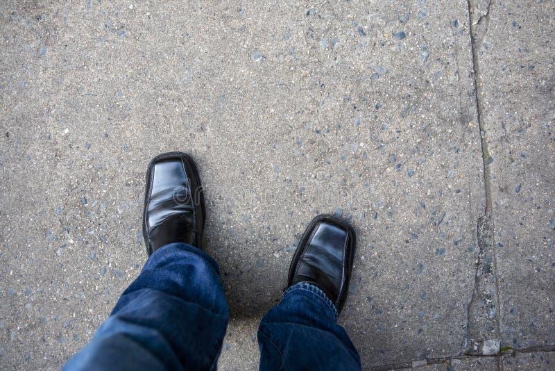 Loooking på mans ner ben med jeans och svarta skor på en stads- stadstrottoargångbana arkivfoto