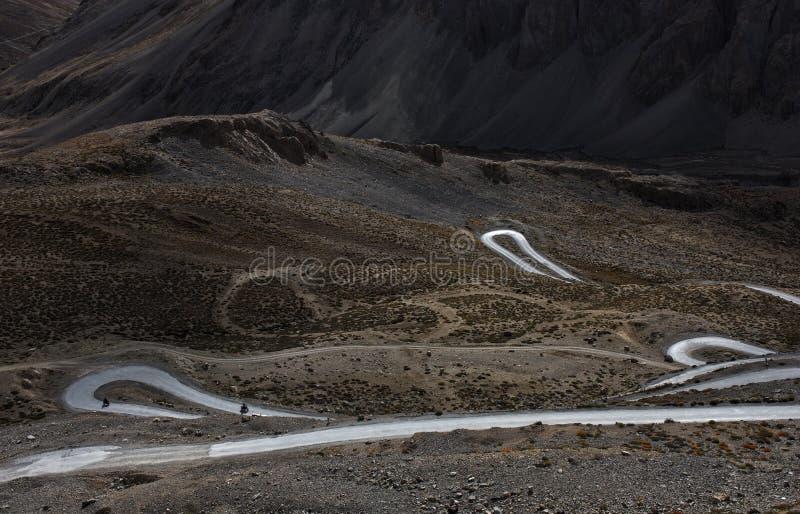 Loop roads with bikers in deep valleys of wilderness land of Ladakh, India stock photo