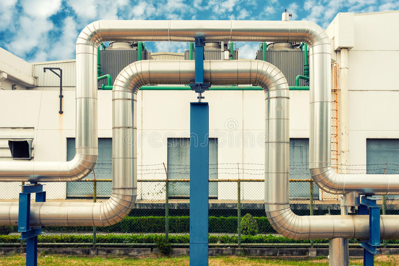 Loop steam pipeline on cooling tower background., Steam insulation. stock photo