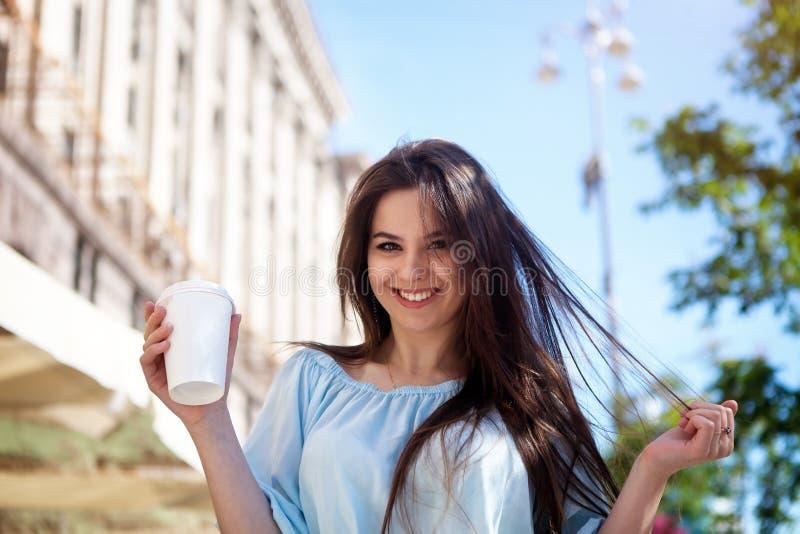 Loopt het portret mooie meisje met lang haar in een toevallige uitrusting in de stad Het mooie brunette houdt koffie stock foto