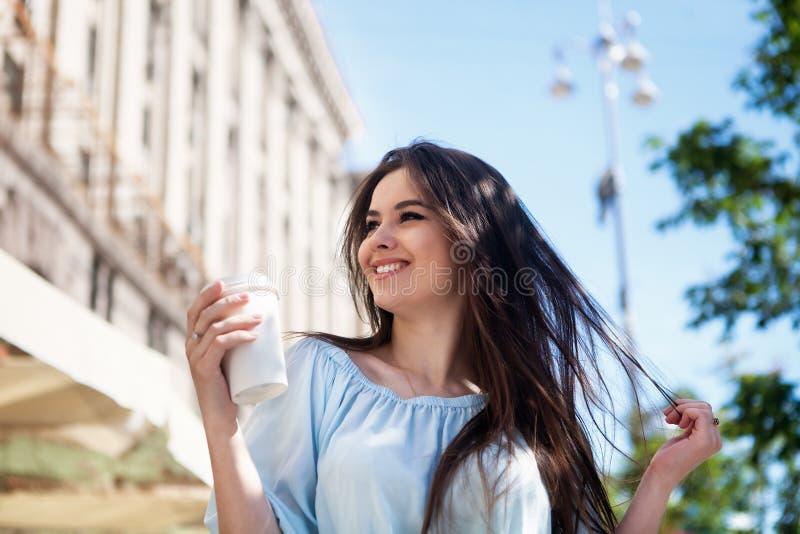 Loopt het portret mooie meisje met lang haar in een toevallige uitrusting in de stad Mooie donkerbruine whithkoffie royalty-vrije stock afbeeldingen
