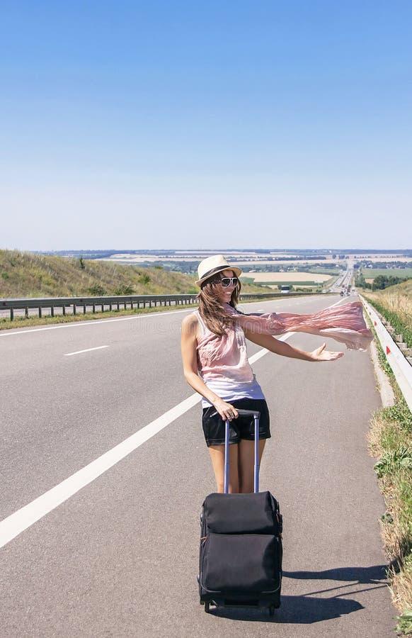 Loopt het reizigers aantrekkelijke glimlachende meisje op weg stock afbeelding