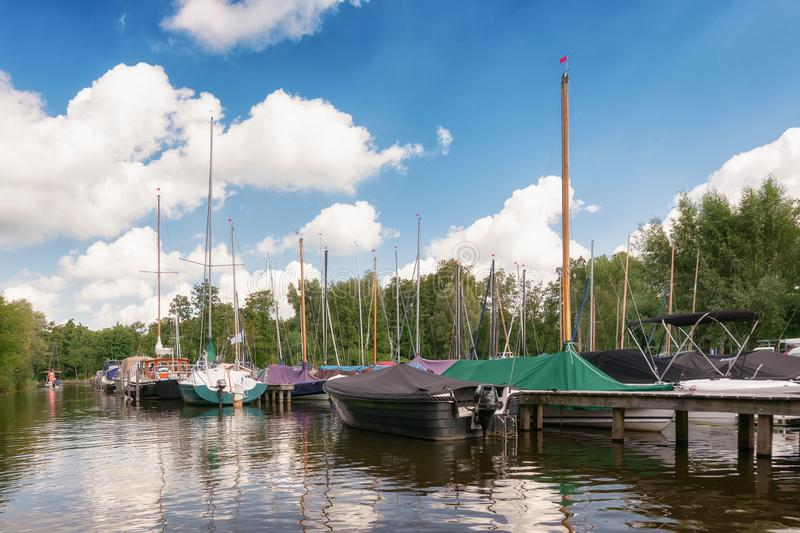 Sailboats and motor boats docked at the jetty of Van Dusseldorf yacht yard royalty free stock image