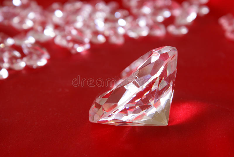 Loose Diamonds. Many loose diamonds with a focal point on a single one up close over a red satin background royalty free stock photo