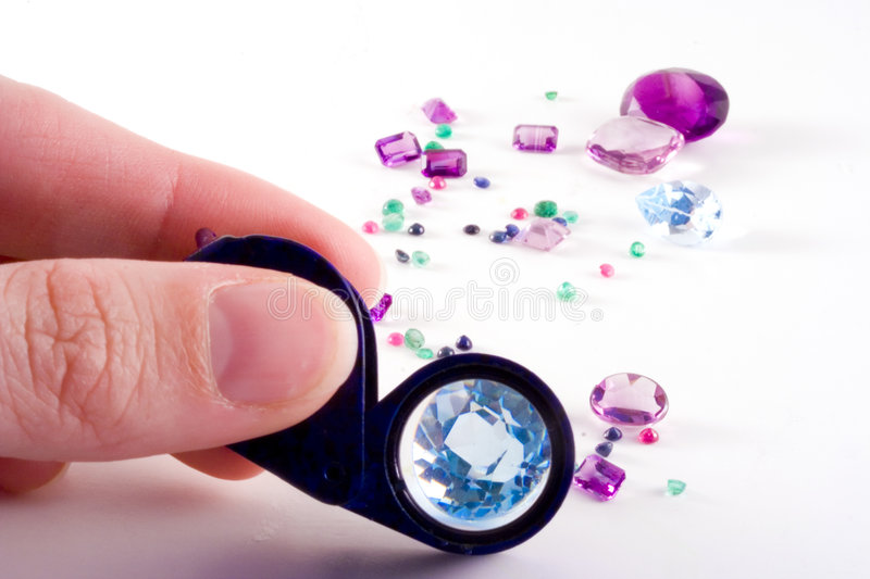 Loose gems,fingers and loupe stock photo