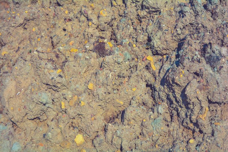 Loose rough dry clay mud with pebbles. Natural texture of dry brown dirty soil. Loose rough dried clay mud with small stones. Natural texture of dry brown dirty stock image