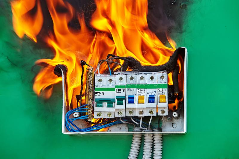 Loose wires caused fire inside electrical fuse box. Bad electrical wiring system in electrical switchboard became the cause of fire. A faulty circuit breaker stock photography