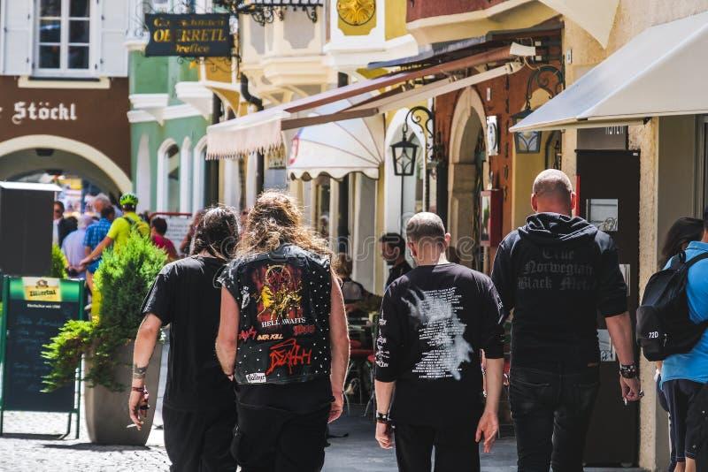 Lopen de fans van het Wacken die Zware Metaal metalheads in straat van achter wordt gezien - Alternatieve muzieklevensstijl royalty-vrije stock afbeeldingen