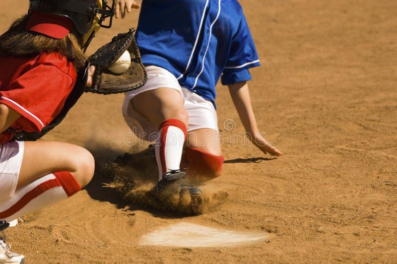 Lopen die van de Speler van het honkbal in Basis glijden stock foto's